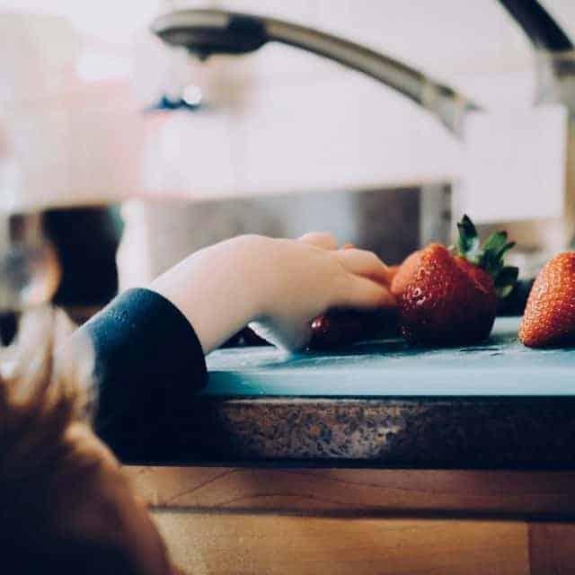 Vegan kid grabbing strawberries