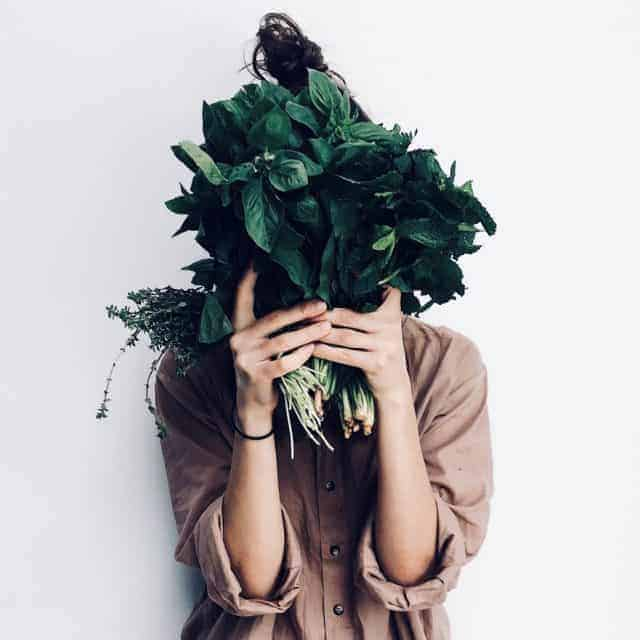 Woman holding iron-rich plants and leafy greens