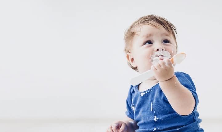 Baby eating vegan probiotic-rich yoghurt