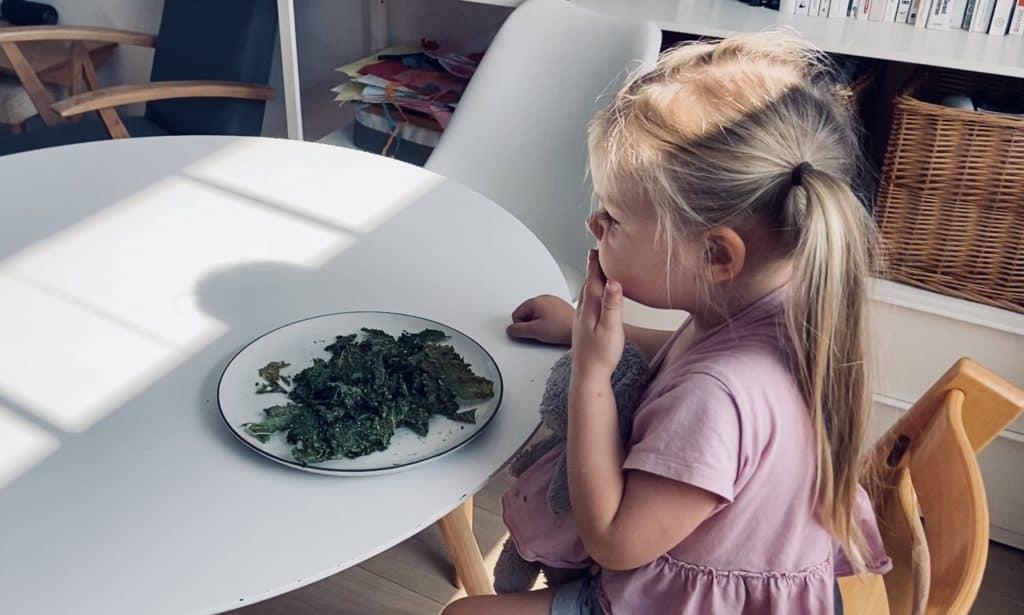 Vegan child eating kale chips