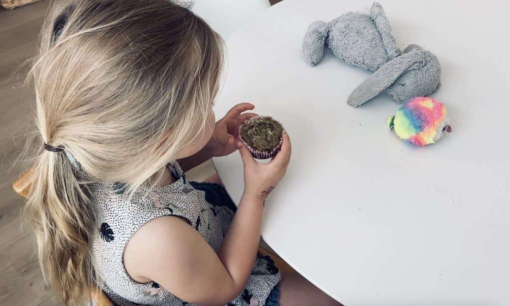 Vegan child eating kale muffin